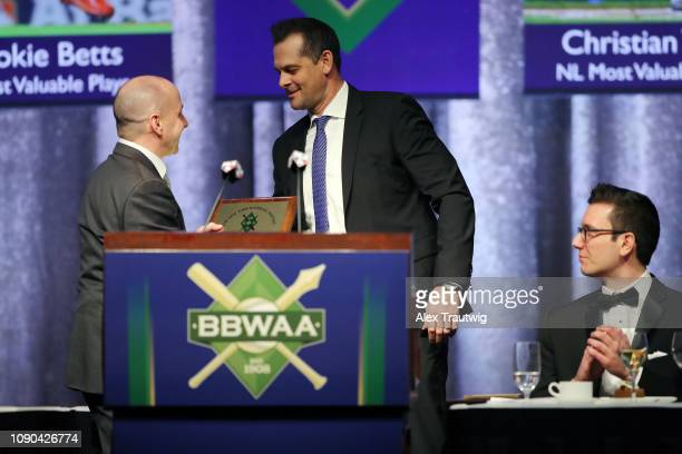 Brian Cashman General Manager of the New York Yankees and winner of the Joan Payson/Shannon Forde Community Service award shakes hands with manager...