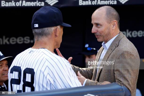 Brian Cashman general manager of the New York Yankees speaks with Joe Girardi of the New York Yankees prior to a game against the Toronto Blue Jays...