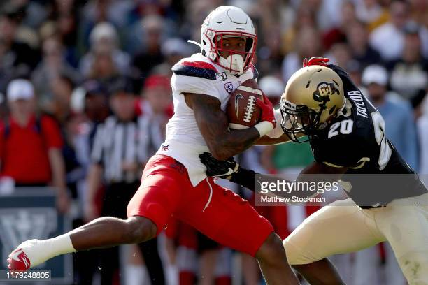 Brian Casteel of the Arizona Wildcats tries to break free from Davion Taylor of the Colorado Buffaloes in the second quarter at Folsom Field on...