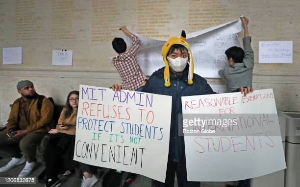 Brian Chen holds two signs during an MIT international student demonstration on March 12 2020 in Cambridge MA Students at the Massachusetts Institute...