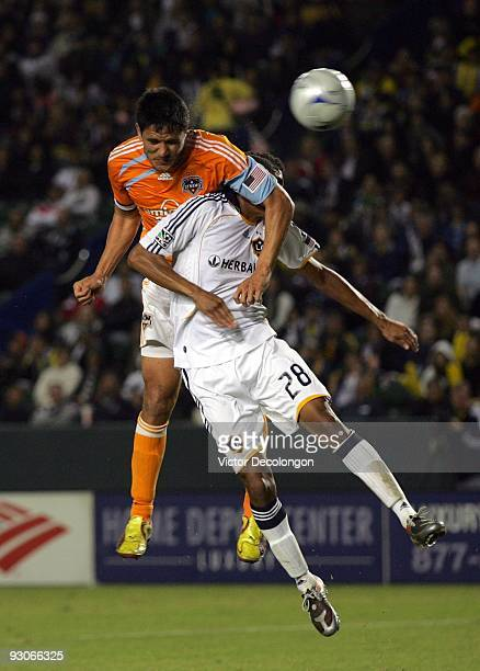 Brian Ching of the Houston Dynamo heads the ball toward the net over Sean Franklin of the Los Angeles Galaxy during the MLS Western Conference...