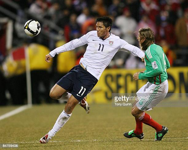 Brian Ching Of USA watches the ball as Leandro Augusto of Mexico closes in during a FIFA 2010 World Cup qualifying match in the CONCACAF region at...