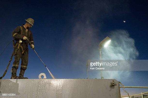 Brian Coffey a floor hand hoses down storage tanks on the Raven Drilling rig grounds near Watford City ND Oct 1 2013 In 2008 the North Dakota oil...