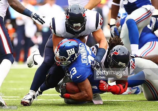 Brian Cushing and DJ Swearinger of the Houston Texans tackle Rashad Jennings of the New York Giants in the first quarter at MetLife Stadium on...