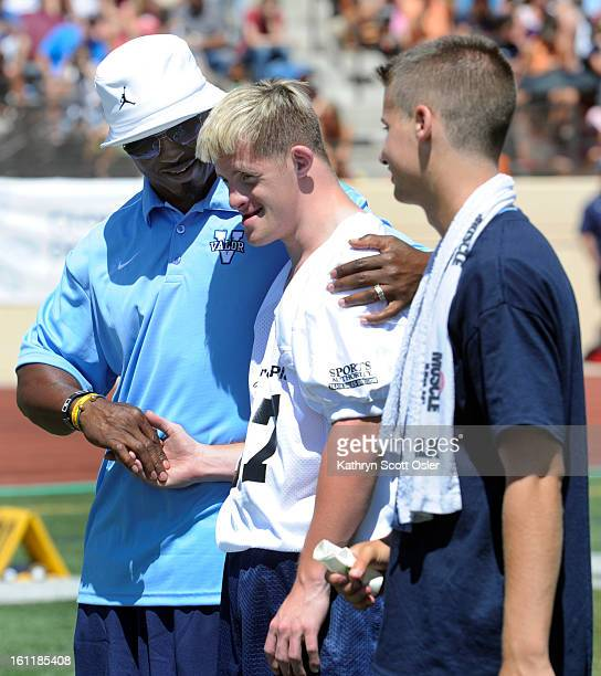 Brian Dawkins left congratulates one of his players Brad Hennefer center after making a touchdown for his team Former Denver Broncos receiver Ed...