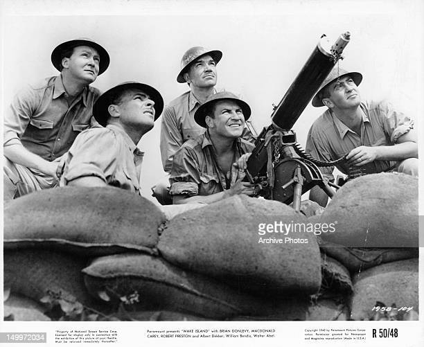 Brian Donlevy Robert Preston and others watching as gunman aims his weapon skyward from the trenches in a scene from the film 'Wake Island' 1942