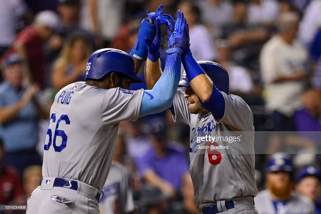 Brian Dozier #6 and Yasiel Puig #66 of the Los Angeles Dodgers celebrate after a two-run home run by Dozier in the ninth inning against the Colorado Rockies at Coors Field on August 9, 2018 in Denver, Colorado.