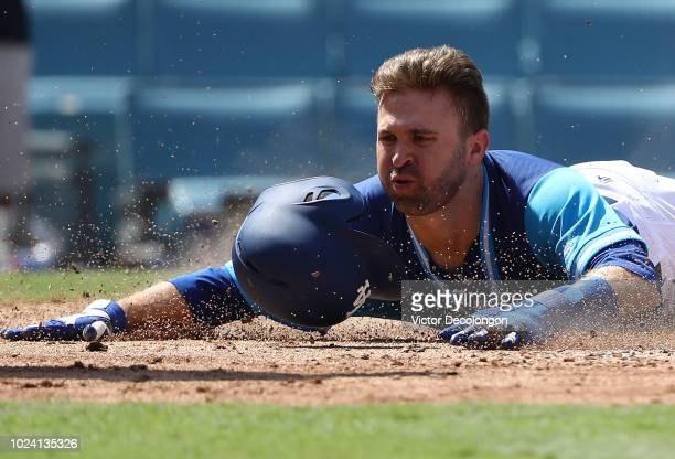 Brian Dozier of the Los Angeles Dodgers finishes his slide into homeplate safely to score during the fifth inning of the MLB game at Dodger Stadium...