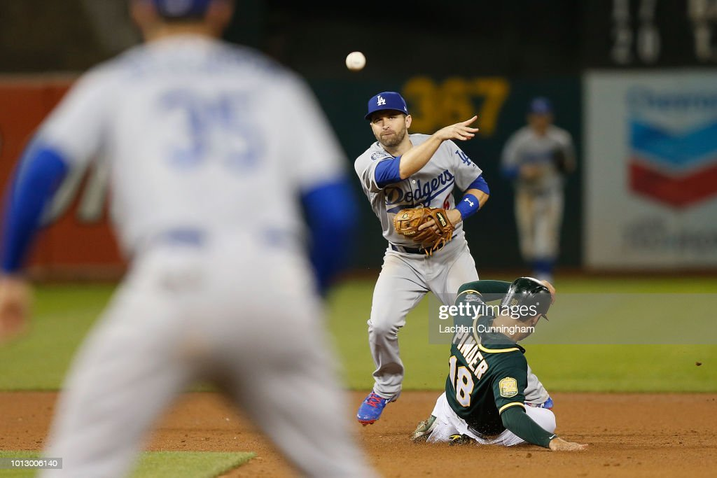 Brian Dozier #6 of the Los Angeles Dodgers gets the out of Chad Pinder #18 of the Oakland Athletics at second base and throws to first base for a double play in the fifth inning at Oakland Alameda Coliseum on August 7, 2018 in Oakland, California.