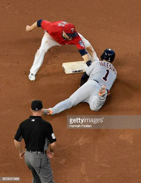 Brian Dozier of the Minnesota Twins catches Jose Iglesias of the Detroit Tigers stealing second base as umpire Will Little looks on during the fourth...