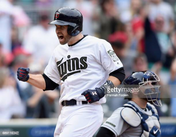 Brian Dozier of the Minnesota Twins celebrates hitting a tworun home run as Derek Norris of the Tampa Bay Rays looks on during the eighth inning of...