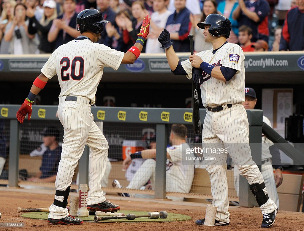 Brian Dozier #2 of the Minnesota Twins congratulates teammate Eddie Rosario #20 on his solo home run in his first career at-bat during the third inning of the game on May 6, 2015 at Target Field in Minneapolis, Minnesota.