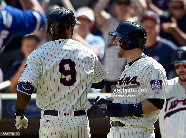 Brian Dozier of the Minnesota Twins congratulates teammate Eduardo Nunez on a threerun home run against the Toronto Blue Jays during the eighth...