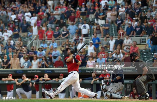 Brian Dozier of the Minnesota Twins hits a walkoff grand slam as Jesus Sucre of the Tampa Bay Rays and home plate umpire Ryan Additon look on during...