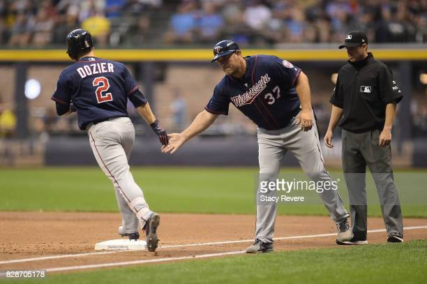 Brian Dozier of the Minnesota Twins is congratulated by first base coach Jeff Smith following a third inning home run against the Milwaukee Brewers...