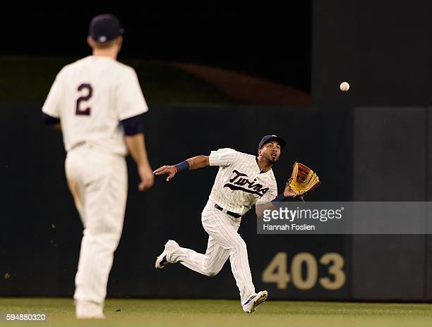 Brian Dozier of the Minnesota Twins looks on as teammate Eddie Rosario makes a catch in center field during the fourth inning of the game against the...