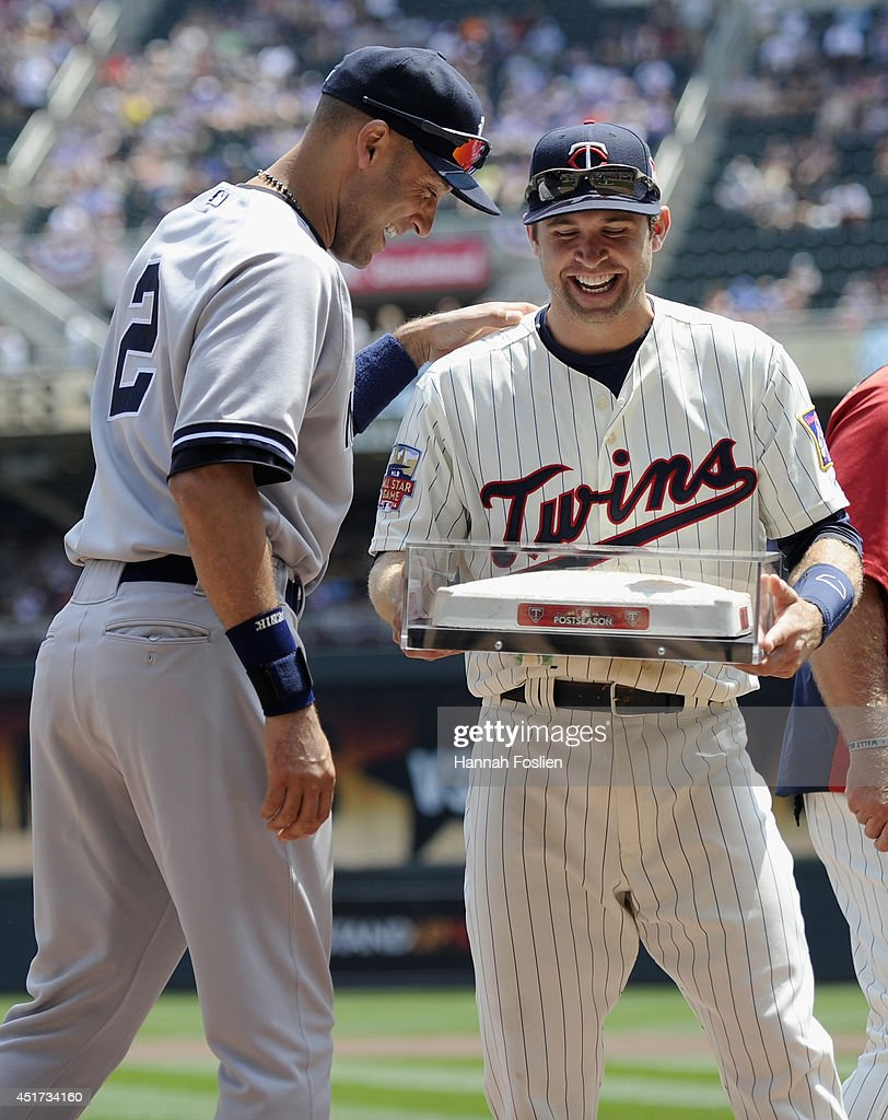 Brian Dozier #2 of the Minnesota Twins presents Derek Jeter #2 of the New York Yankees with the last second base used at the Metrodome before the game on July 5, 2014 at Target Field in Minneapolis, Minnesota.