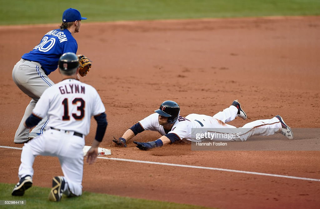 Brian Dozier #2 of the Minnesota Twins slides into third base safely against Josh Donaldson #20 of the Toronto Blue Jays as third base coach Gene Glynn #13 of the Minnesota Twins looks on during the first inning of the game on May 19, 2016 at Target Field in Minneapolis, Minnesota.