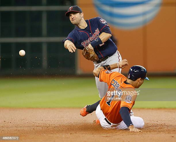 Brian Dozier of the Minnesota Twins throws over Carlos Correa of the Houston Astros to complete a double play in the first inning at Minute Maid Park...