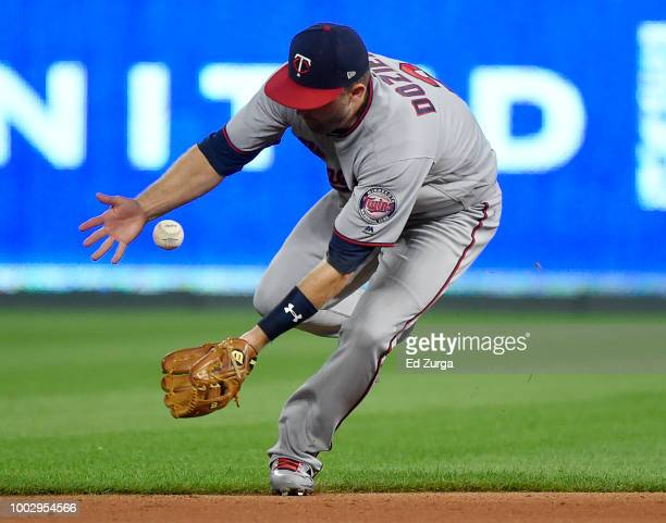 Brian Dozier of the Minnesota Twins tries to get a glove on a ball hit by Alcides Escobar of the Kansas City Royals in the seventh inning at Kauffman...