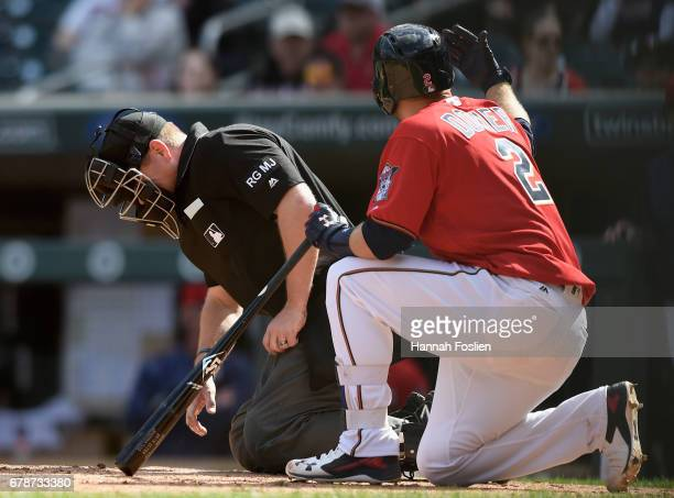 Brian Dozier of the Minnesota Twins waves for a trainer for home plate umpire Mike Muchlinski after he was hit by a foul ball during the ninth inning...