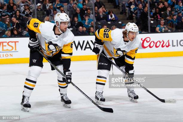 Brian Dumoulin and Carl Hagelin of the Pittsburgh Penguins face off against the San Jose Sharks at SAP Center on January 20 2018 in San Jose...