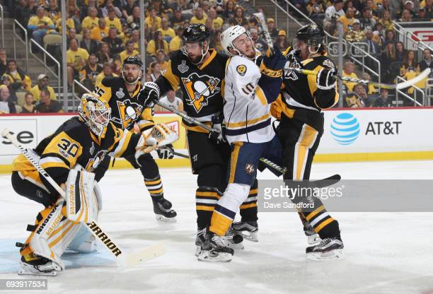 Brian Dumoulin and Evgeni Malkin of the Pittsburgh Penguins defend Colton Sissons of the Nashville Predators in front of goaltender Matt Murray...