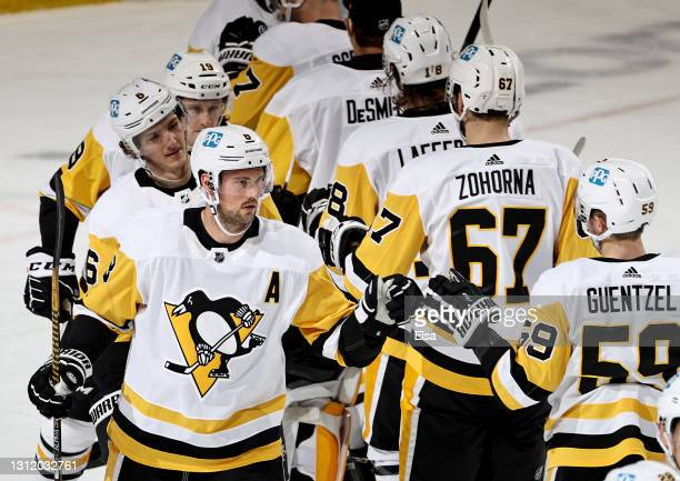 Brian Dumoulin and Jake Guentzel of the Pittsburgh Penguins celebrate the win over the New Jersey Devils at Prudential Center on April 11, 2021 in...