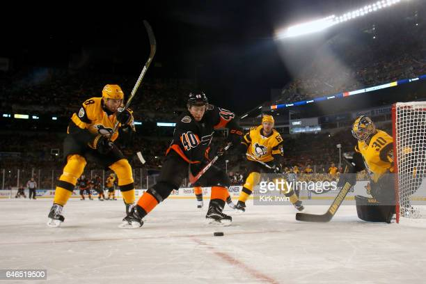 Brian Dumoulin of the Pittsburgh Penguins and Jordan Weal of the Philadelphia Flyers chase after a loose puck during the game at Heinz Field on...