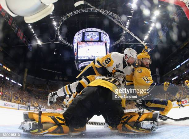 Brian Dumoulin of the Pittsburgh Penguins and Mike Fisher of the Nashville Predators collide and fall over goaltender Matt Murray during the second...