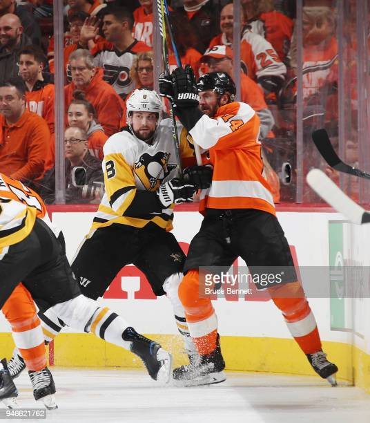 Brian Dumoulin of the Pittsburgh Penguins and Sean Couturier of the Philadelphia Flyers battle for position during the first period in Game Three of...