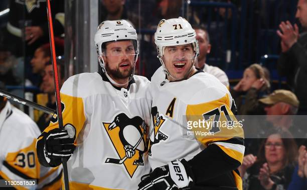 Brian Dumoulin of the Pittsburgh Penguins celebrates his second period goal against the Buffalo Sabres with Evgeni Malkin during an NHL game on March...