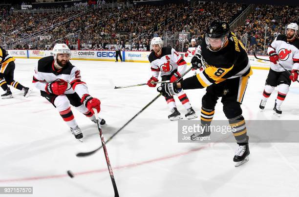 Brian Dumoulin of the Pittsburgh Penguins clears a puck against Kyle Palmieri of the New Jersey Devils at PPG Paints Arena on March 23 2018 in...