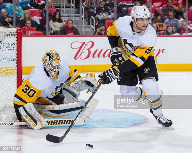 Brian Dumoulin of the Pittsburgh Penguins controls the puck in front of teammate Matt Murray during an NHL game against the Detroit Red Wings at...