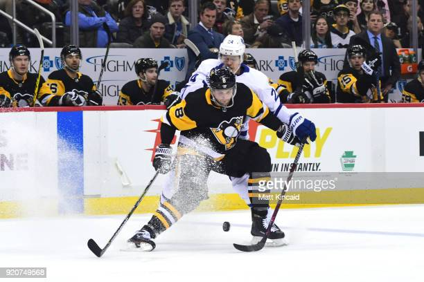 Brian Dumoulin of the Pittsburgh Penguins fights for the puck against Kasperi Kapanen of the Toronto Maple Leafs at PPG PAINTS Arena on February 17...