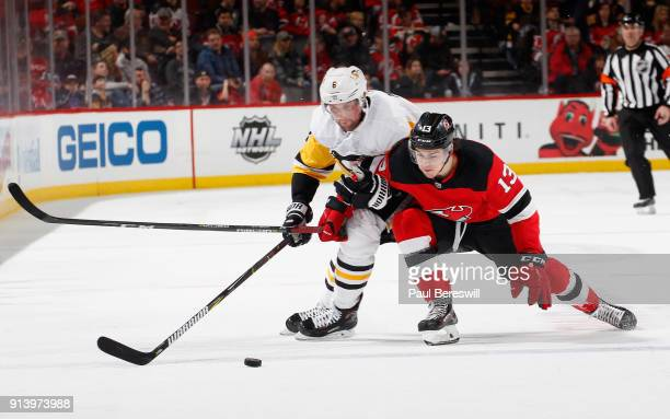 Brian Dumoulin of the Pittsburgh Penguins grabs Nico Hischier of the New Jersey DeviMathew Barzal of the New York Islanders tp slow him down in an...