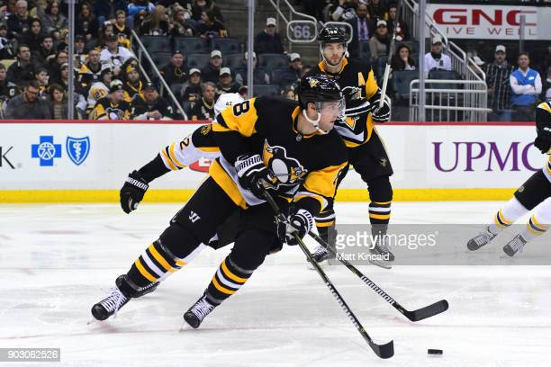 Brian Dumoulin of the Pittsburgh Penguins skates with the puck against the Boston Bruins at PPG PAINTS Arena on January 7 2018 in Pittsburgh...