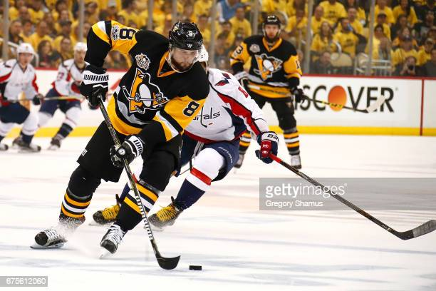 Brian Dumoulin of the Pittsburgh Penguins tries to turn up ice in front of Alex Ovechkin of the Washington Capitals during the first period in Game...