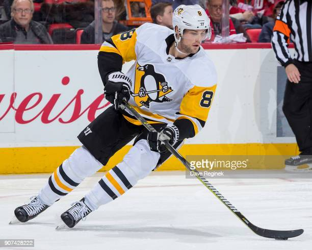 Brian Dumoulin of the Pittsburgh Penguins turns up ice with the puck against the Detroit Red Wings during an NHL game at Little Caesars Arena on...