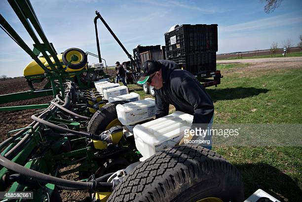 Brian Dunseth unloads containers of insecticide from a Deere Co John Deere 24row planter during corn planting in Malden Illinois US on Tuesday May 6...
