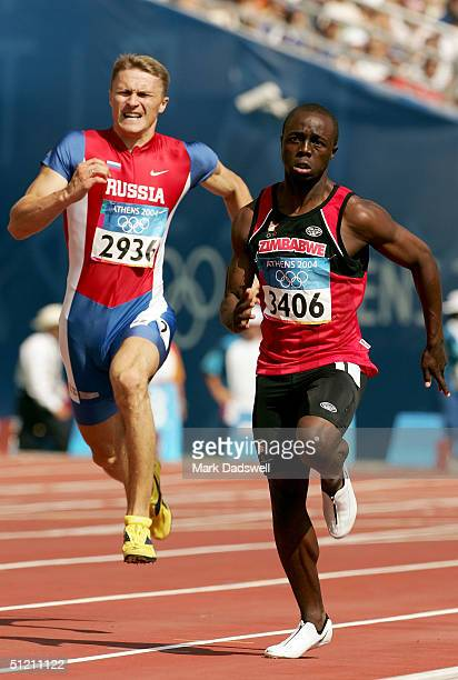 Brian Dzingai of Zimbabwe and Oleg Sergeyev of Russia compete in the men's 200 metre on August 24 2004 during the Athens 2004 Summer Olympic Games at...