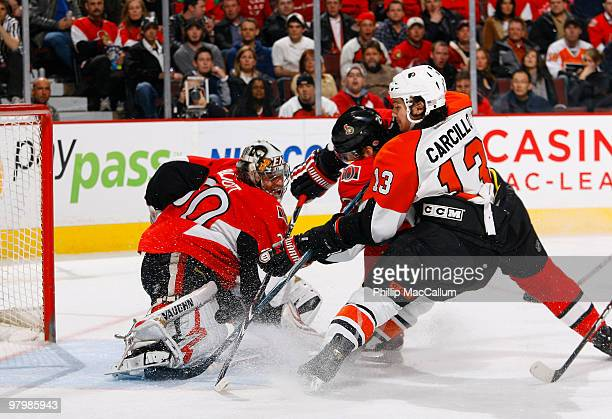 Brian Elliot of the Ottawa Senators makes a pad save while teammate Anton Volchenkov battles with Dan Carcillo of the Philadelphia Flyers for the...