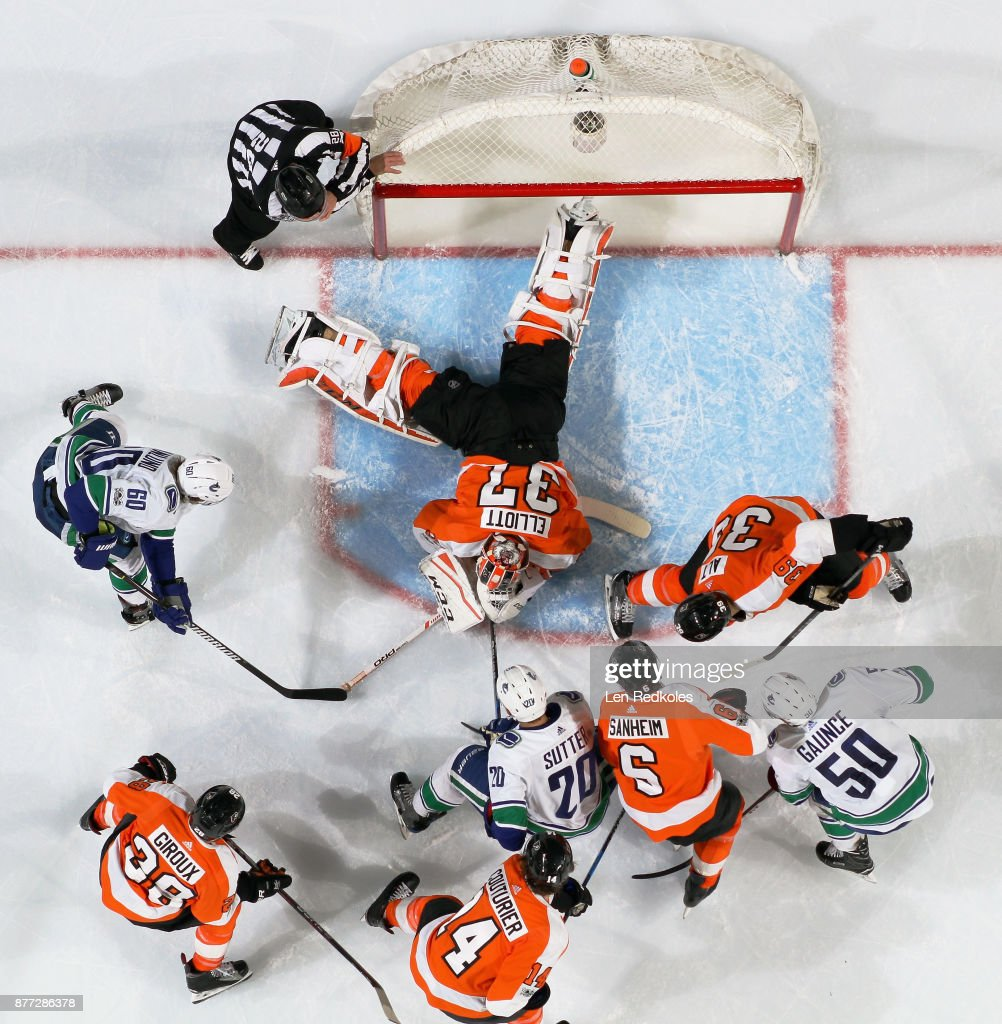 Brian Elliot #37 of the Philadelphia Flyers covers the puck as teammates Mark Alt #39, Travis Sanheim #6, Sean Couturier#14, and Claude Giroux #28 battles against Brendan Gaunce #50, Brandon Sutter #20, and Markus Granlund #60 of the Vancouver Canucks on November 21, 2017 at the Wells Fargo Center in Philadelphia, Pennsylvania. The Canucks went on to defeat the Flyers 5-2.