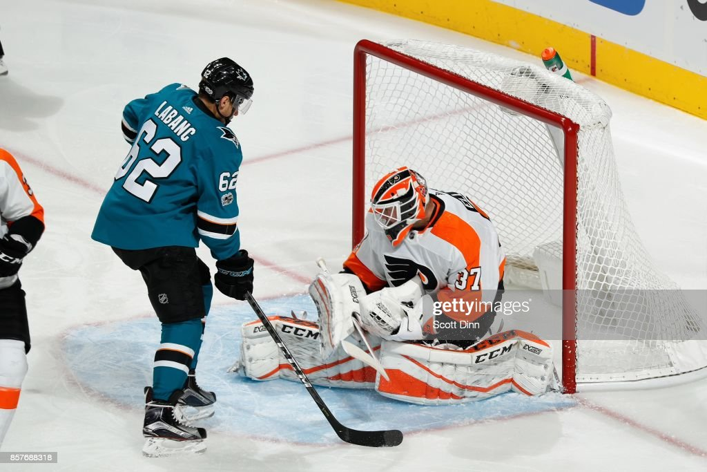 Brian Elliot #37 of the Philadelphia Flyers makes a save as Kevin Labanc #62 of the San Jose Sharks follows the puck during a NHL game at SAP Center at San Jose on October 4, 2017 in San Jose, California.
