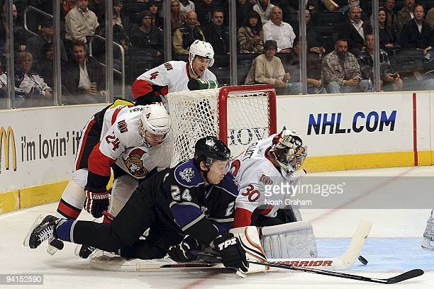 Brian Elliott and Anton Volchenkov of the Ottawa Senators defend the net from a shot by Alexander Frolov of the Los Angeles Kings during the game on...