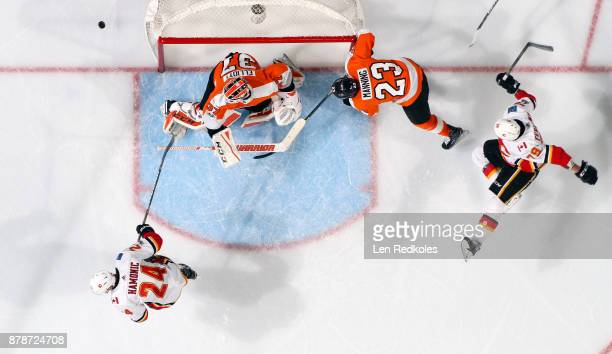 Brian Elliott and Brandon Manning of the Philadelphia Flyers react to a puck shot wide of the net against Travis Hamonic and Micheal Ferland of the...