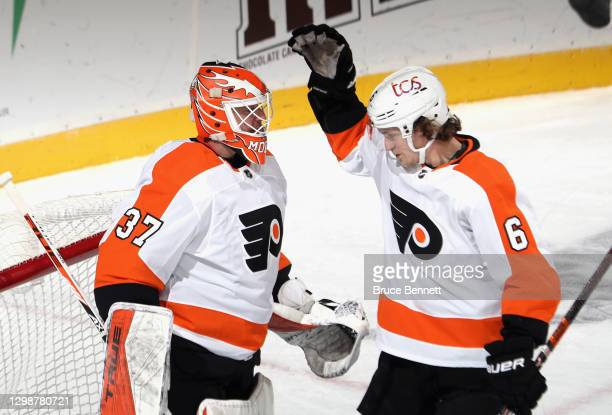 Brian Elliott and Travis Sanheim of the Philadelphia Flyers celebrate their 5-3 victory over the New Jersey Devils at the Prudential Center on...