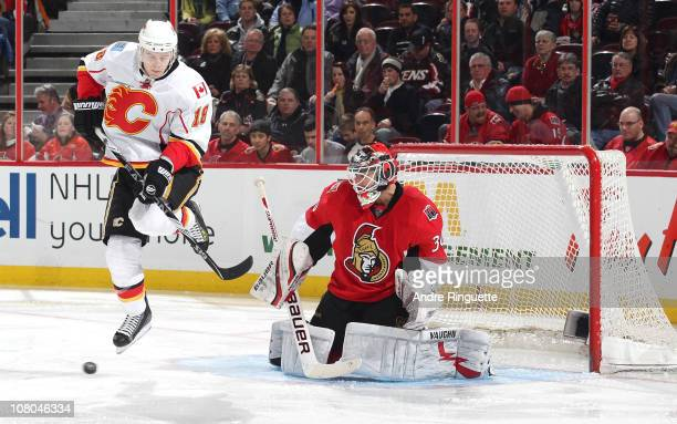 Brian Elliott of the Ottawa Senators guards his net as Matt Stajan of the Calgary Flames jumps out of the way of a shot at Scotiabank Place on...