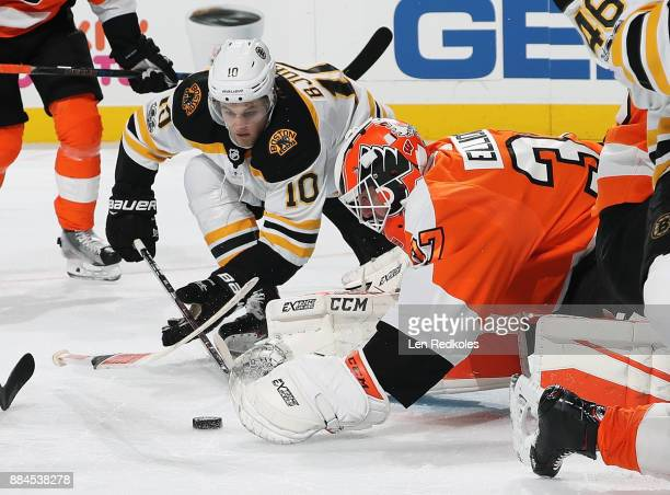 Brian Elliott of the Philadelphia Flyers and Anders Bjork of the Boston Bruins dive towards the loose puck on December 2 2017 at the Wells Fargo...