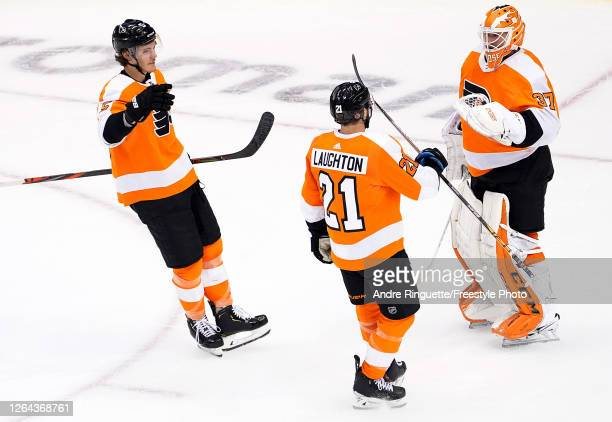 Brian Elliott of the Philadelphia Flyers celebrates with Scott Laughton and Philippe Myers after defeating the Washington Capitals in the Eastern...